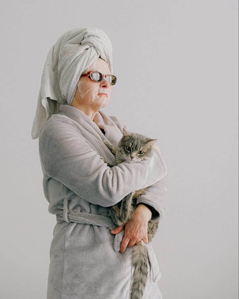 Lady in robe mask and towel holding a cat