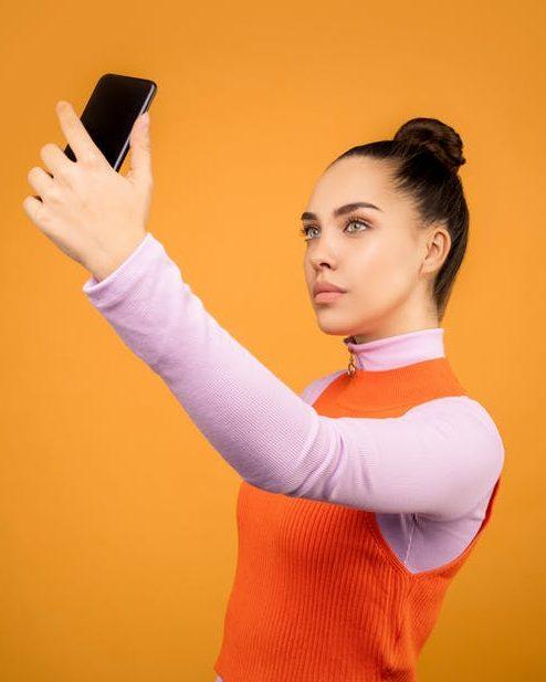 Girl in tight hair bun taking selfies